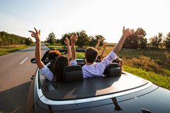 Free Black Cabriolet Is On The Country Road. Company Of Young Girls And Guys Are Sitting In The Car Hold Their Hands Up On A Stock Photography - 138707002