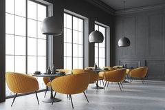 Corner of a black cafe. Black cafe corner with a concrete floor, round black tables and yellow chairs. 3d rendering mock up Stock Photography