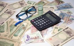 Black calculator and blue ballpoint pen and Spectacles with roll Thai banknotes use a rubber band on the various nations banknotes royalty free stock image