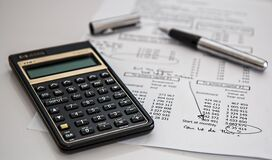 Black Calculator Near Ballpoint Pen on White Printed Paper Royalty Free Stock Photography