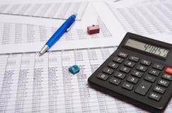Black calculator, pen, small house Stock Image