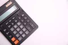 Black calculator on the side on white background stock photos