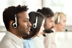 Black call center operator with colleagues. Side view of line of call centre employees are smiling and working on computers Stock Photo