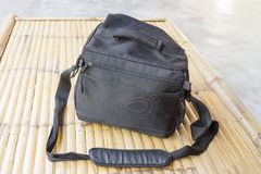 Black camera bag on bamboo floor Royalty Free Stock Photo