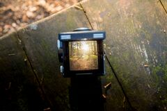 Black Camera on Brown Wooden Table Stock Images