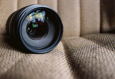Black Camera Lens on Brown Textile Stock Photo