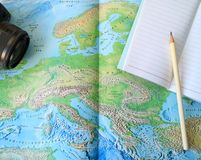 Black Camera and Lined Notebook with White Pencil on the World Map royalty free stock photos