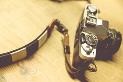 Black Camera With White and Black Strap on Beige Surface Royalty Free Stock Image