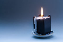 Black candle with a flame and drips. Dark blue gradient background. Greeting holiday card template. copy space Stock Images