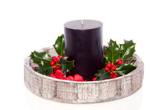 Black candle with holly Stock Photos