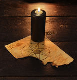 Black candle with pentacle. Black candle with pentagram on wooden table. Halloween and magic still life, fortune telling seance or black magic ritual with Stock Photo