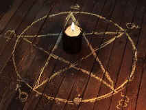 Black candle in pentagram circle. Black candle in pentagram on wooden planks. Magic ritual with occult, evil and esoteric symbols. Scary halloween rite Stock Photography