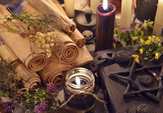 Black candles with old parchments and evil magic book with pentagram on cover Stock Images
