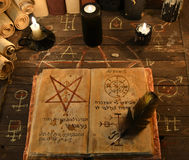 Black candles and open magic book with pentagram. Black candles, scrolls and open magic book with pentagram on wooden table. Halloween concept, black magic Stock Photos