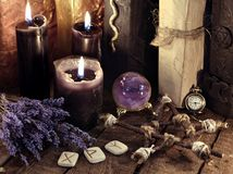 Black candles, pentagram, runes and lavender flowers with crystal ball. Occult, esoteric, divination and wicca concept. Mystic and vintage background with old royalty free stock photos