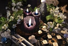 Black candles with runes, zodiac circle and spring flowers. Occult, esoteric and divination still life. Halloween background with vintage objects and magic Stock Photography
