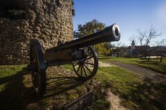 Black Cannon in Front of the Brick Wall Building Royalty Free Stock Image