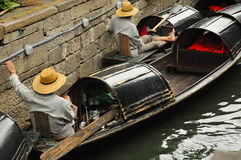 Black Canopied Boats Shaoxing. Chinese oarsmen sitting in the wu peng chuan or the black canopied boats on the canals of Lu Xun native place in the city of Royalty Free Stock Photo