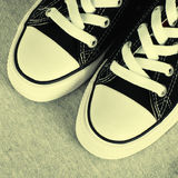 Black canvas sneakers on grey textile background Royalty Free Stock Images