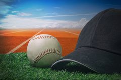 Black cap and a baseball on a green grass with a red running track. And blue sky Royalty Free Stock Photography