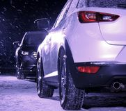 Two vehicles opposites prevent the collision at night. Black car against white car on the snow road at night stock photos