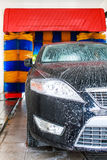 Black car in automatic car wash, rotating blue and yellow brushes visible. Car being washed in automatic car wash, rotating blue and yellow brushes visible stock photos