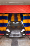 Black car in automatic car wash, rotating blue and yellow brushes visible. Car being washed in automatic car wash, rotating blue and yellow brushes visible royalty free stock photography