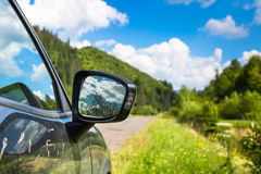 Summer Car trip road travel concept. Black car on the background of the road and mountain scenery. Summer Car trip road travel concept Royalty Free Stock Images