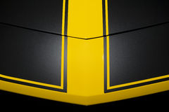 Black car bodywork. Surface of black sport sedan car metal hood with yellow arrow lines, part of vehicle bodywork Royalty Free Stock Photos