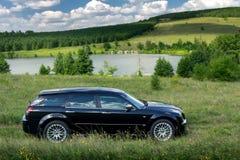 Black car Chrysler 300c stand off-road near lake at daytime Royalty Free Stock Images