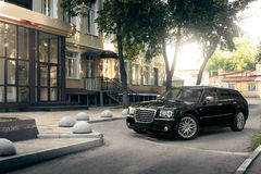 Black car Chrysler 300c standing on asphalt road in the city at daytime. Saratov, Russia - August 9, 2015: Black car Chrysler 300c standing on asphalt road in Stock Photography