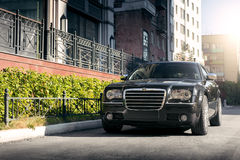 Black car Chrysler 300c standing on asphalt road in the city at daytime. Saratov, Russia - August 9, 2015: Black car Chrysler 300c standing on asphalt road in Royalty Free Stock Photo