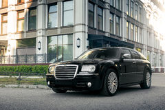 Black car Chrysler 300c standing on asphalt road in the city at daytime. Saratov, Russia - August 9, 2015: Black car Chrysler 300c standing on asphalt road in Royalty Free Stock Photos