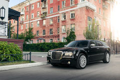 Black car Chrysler 300c standing on asphalt road in the city at daytime. Saratov, Russia - August 9, 2015: Black car Chrysler 300c standing on asphalt road in Stock Photos
