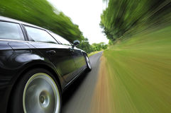 Black car in countryside. Side view of black car on tree lined countryside road with blur effect background Royalty Free Stock Photo