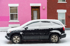 Black car covered with snow in front of pink traditional house during snow storm Royalty Free Stock Photo
