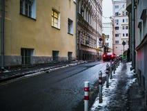Black Car Crossing Asphalt Road Between Buildings Stock Images