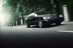 Black car drive on asphalt road in nature park of city at daytime Stock Photo