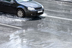 Black car driving through water puddles on city street after rai Royalty Free Stock Images