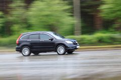 Black car is driving on a wet road. Summer morning Stock Photography