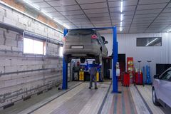 Black car in garage with special equipment prepared for repair stock image