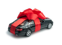 Black car for a gift with a red bow. New black car for a gift with a red bow and ribbon isolated on a white background Royalty Free Stock Photos
