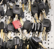 Black car keys and a red one on a special wall. In a key cutting workshop royalty free stock photography