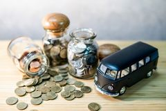 Saving money for car buying. Auto loan concept. Black car model with coin in currency glass jar and spilling out on wooden table. Car loan interest rate. Saving royalty free stock photo