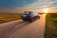 Black car in motion blur on open road