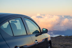 Black car in mountains above the clouds at sunset or sunrise Stock Photo