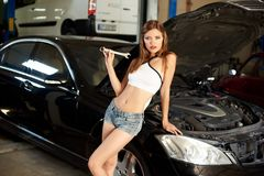 Black car with open hood and girl leaned against him. Black car with an open hood and an attractive girl leaned against him in the garage. The girl is openly Stock Image