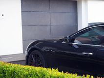 Black Car Parked in Driveway. A modern black car parked in driveway outside house garage, with small green boundary hedge stock images