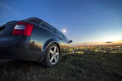 Black car parked at night in green meadows on copy space background of lights of distant city buildings and bright blue sky with. First star at sunset stock image