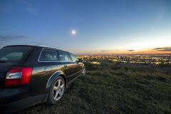 Black car parked at night in green meadows on copy space background of lights of distant city buildings and bright blue sky with. First star at sunset royalty free stock photo